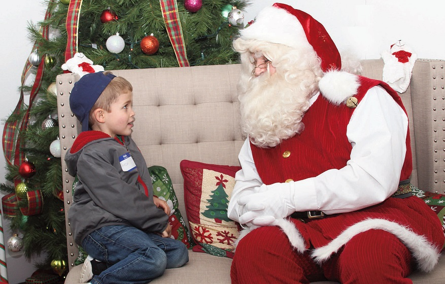 Harrison Timmins, 4, of Waterville, talks with Santa Claus at Kringleville, in downtown Waterville, recently. Santa is available for boys and girls to visit at his Christmas home located at The Center, on Main Street. Photo by Central Maine  Photography staff