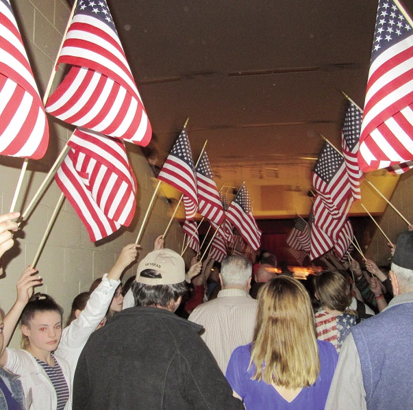 Students form a canopy of American flags as military veterans are escorted into the auditorium by students
